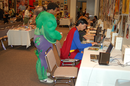 Two men gather round a computer in the press room at south by southwest, one dressed as superman, one as the incredible hulk