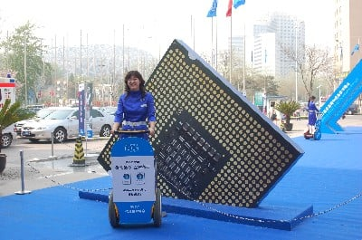 Shot of women on a Segway by a large replica of an Intel chip
