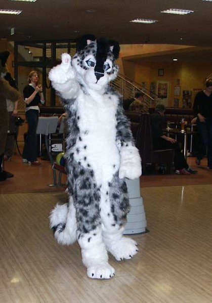 black and white feline furry on dance floor, giving thumbs up to camera