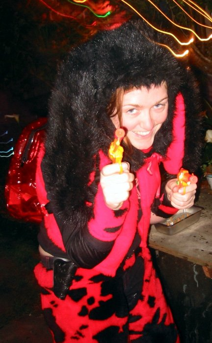 Female 'headless' furry in red costume - indeterminate animal - semi-crouching, smiling with water-pistol in hand