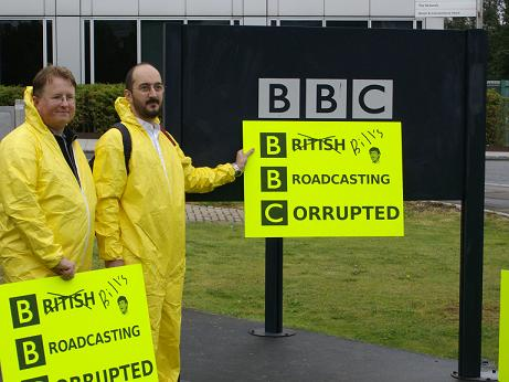 Free software protestors hold up their sign against the BBC's White City sign