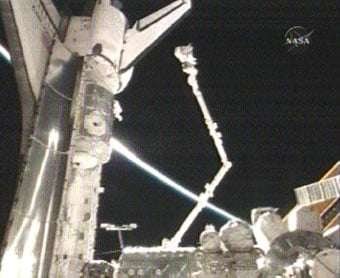 An astronaut on the end of a robotic arm. Credit: NASA TV