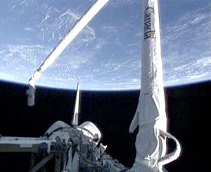 Discovery's robotic arm deployed. Pic NASA