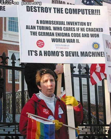 Gay right protester holding banner decrying the homo devil machine