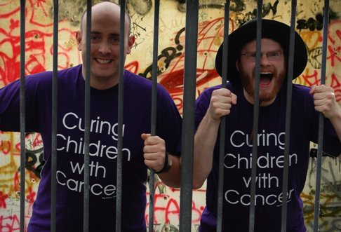 Dave Wood and Simon Painter wearing purple t-shirts with kidscan message, behind prison bars.