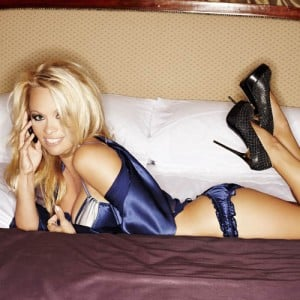 Pamela Anderson lying on bed wearing purple lingerie and black stilettos