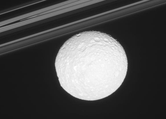 'The bright, icy moon [Mimas] in front of Saturn's delicate rings'. Image credit: NASA/JPL/SSI