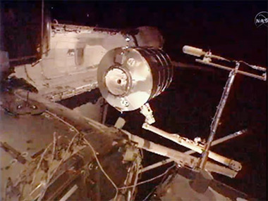 The PMM, attached to the station's robotic arm, is removed from Discovery's payload bay. Pic: NASA TV