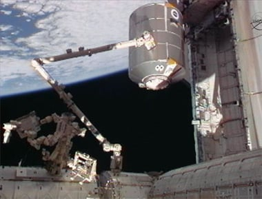 The station's robotic arm, Canadarm2, operated by STS-135 astronauts Doug Hurley and Sandy Magnus, grapples the Raffaello multipurpose logistics module from the shuttle's payload bay. Pic: NASA TV 