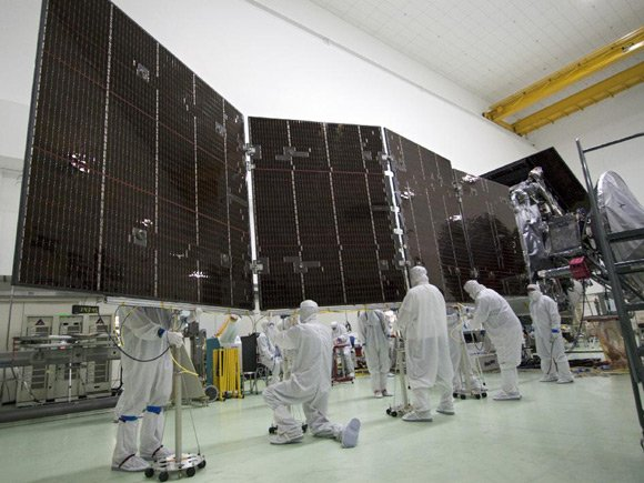 Technicians at Astrotech's payload processing facility in Titusville, Florida, stow solar array number 2 against the body of NASA's Juno spacecraft, NASA explains