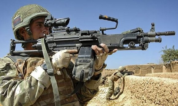 A soldier from the Scots Guards pictured with a Light Machine Gun (LMG) near the village of Inzgule, Helmand, Afghanistan. Credit: Cpl Mark Webster/Crown Copyright
