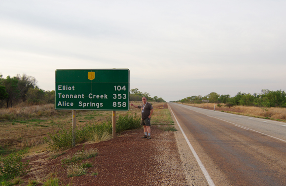 Lester Haines besides a roadsign on the Stuart Highway