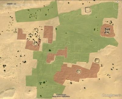 Satellite image of desert with archaeological interpretation of features: fortifications in black, dwellings in red an