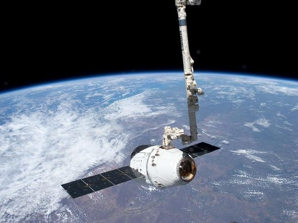 SpaceX Dragon on the Canadarm over Earth