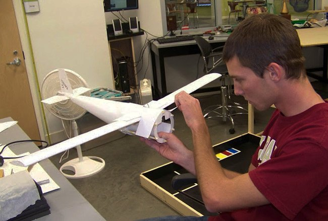 A student works on the skinning of the USI plane
