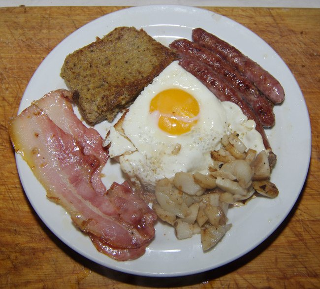 A hearty breakfast of scrapple, fried egg on toast, bacon, sausage and fried mushrooms