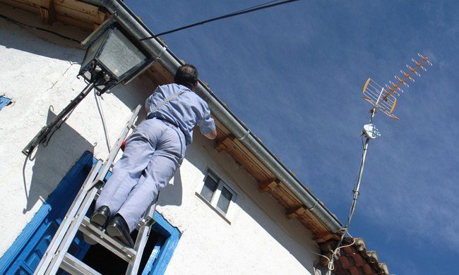Man up ladder installing the Iberbanda receiver