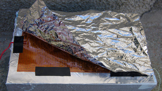The heater on top of an aluminium sheet, with space blanket on top