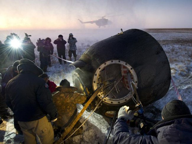 Russian support personnel work to help get crew members out of the Soyuz TMA-02M spacecraft shortly after the capsule landed with Expedition 29 Commander Mike Fossum and flight engineers Ser