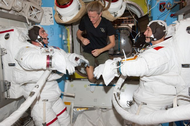 Flight Engineer Karen Nyberg assists FE Chris Cassidy and FE Luca Parmitano in spacewalk prep