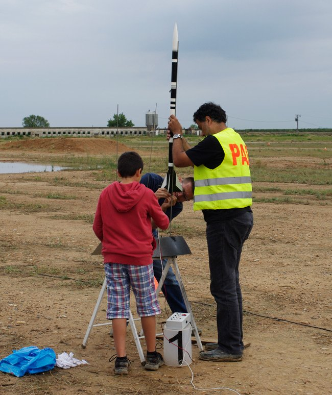 Three rocketeers mount their rocket on the launch rail