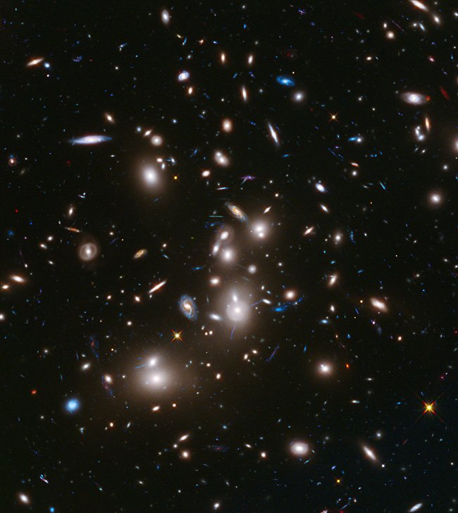 Long-exposure Hubble Space Telescope image of massive galaxy cluster Abell 2744 (foreground) and some of the faintest and younges