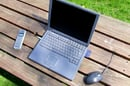 Laptop on a picnic table outside, green grass in background