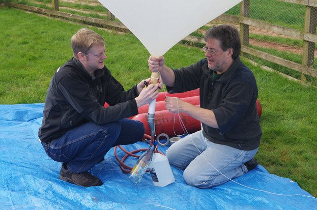 Dave and Anthony tie off the filled balloon