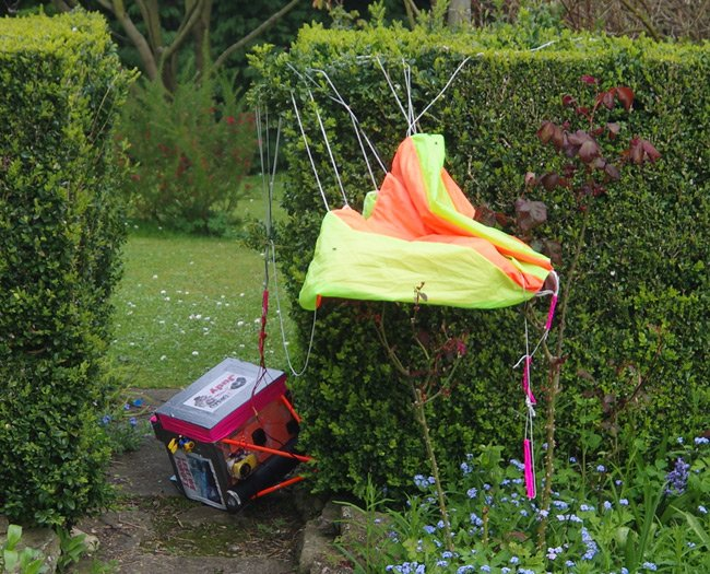 The payload and parachute in a garden hedge