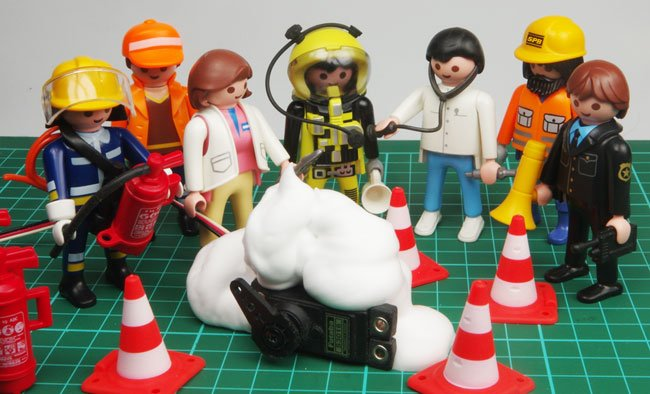 The servo doused in foam as a fireman, doctors and workers gather around our Playmonaut