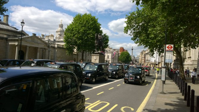 Black cabs crawl along Whitehall