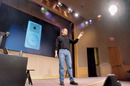 Steve Jobs presents the iPod to an audience of press and Apple employees