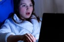 Woman in bathrobe is shocked by something she is reading on her laptop. Pic via Shutterstock