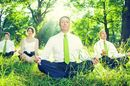 Business types meditate in green field. Photo via Shutterstock