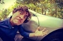 Man gesticulates furiously in front of parked car. Photo by Shutterstock