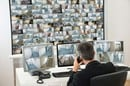 Security guard watches footage from hundreds of camera. Photo by Shutterstock