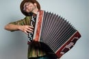Hipster guy plays accordion. Photo by Shutterstock