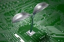 Metal plant grows out of circuit board - Green IT concept pic. Photo by Shutterstock