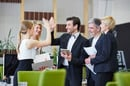 Colleague high fives in the office. Photo by Shutterstock