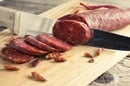 Sharp knife slices at a salami as previously sliced pieces lay on the chopping board. Photo by Shutterstock