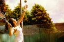 Woman serves at beginning of tennis game. Photo by Shutterstock