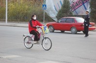 Shot of a girl with a mask biking through Beijing