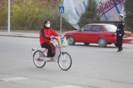 Shot of a girl with a mask biking through Beijing