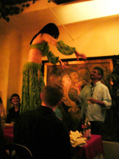 Belly dancer on table in Tunis restaurant. Three men are watching. Two are sitting down. One man is standing