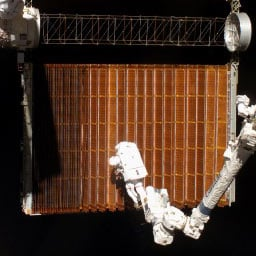 A spacewalker works on a section of solar panelling