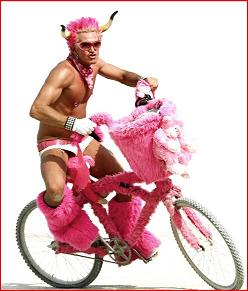 Shot of pink haired Styn shirtless on a pink bike
