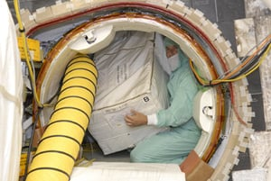 Technician loading ISS toilet spares onto Discovery