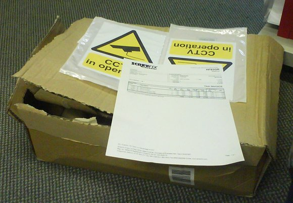 Two CCTV warning signs in an excessively large box