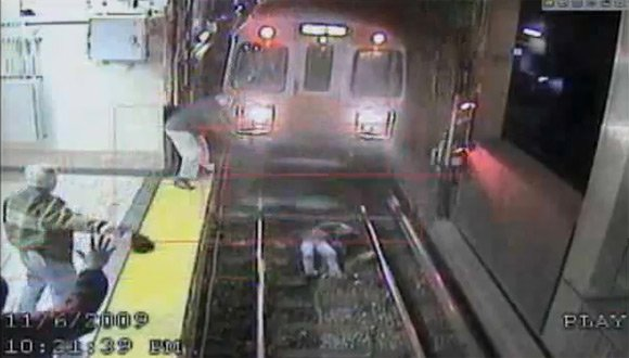 The train comes to a halt as the woman lies on the track