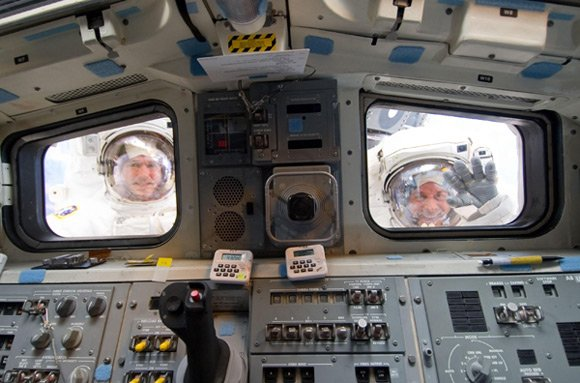 Michael Good (left) and Garrett Reisman caught through the windows of Atlantis. Pic: NASA